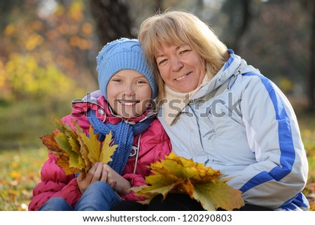 Portrait of teenager girl and senior woman (grand mather) in autumn park