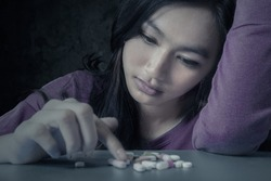 Portrait of teenager girl choosing pills with stressful expression, symbolizing a drugs addict