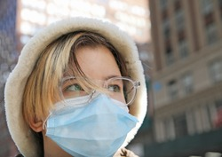 Portrait of teenager girl with short hair, in a winter hat, eyeglasses and a face mask on New York City street on a sunny day,