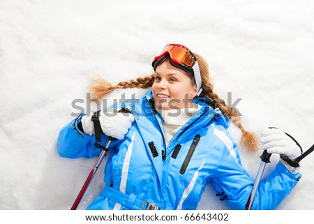 Portrait of teenager holding skiing sticks and lying on snow
