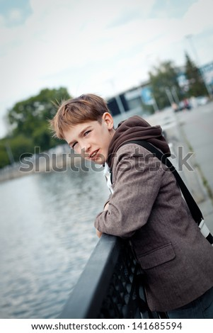 Portrait of teenager on background of river, outdoor