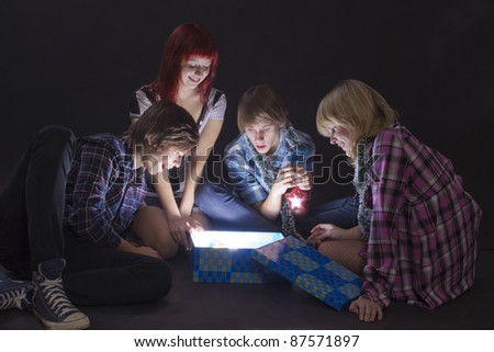 Portrait of  teenagers looking in a magic lighting box - stock photo