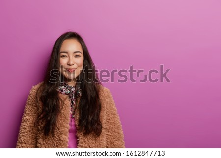 Portrait of tender brunette lady has charming look, smiles gently, wears silk scarf around neck, fur coat, gazes charmed at camera, models against vivid background, copy space area for your text