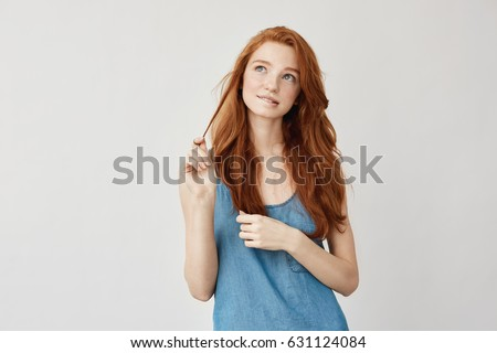 Portrait of tender dreamy freckled ginger girl thinking, feeling insecure about her first date. Growing up into gorgeous young woman. Planning out on white background. Twenties concept. #631124084