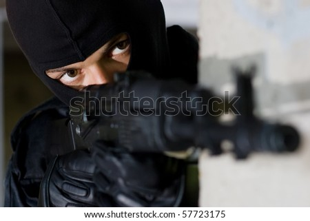 Portrait of terrorist in black mask aiming with automatic AK 47 rifle. Focus on eyes. Armed man in black uniform from Ukraine