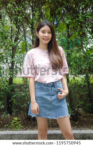 Portrait of thai adult beautiful girl pink shirt blue jeans relax and smile #1195750945