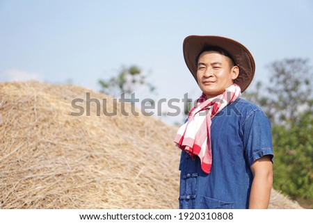 Portrait of Thai male farmer wearing hat and loincloth scarf on his neck  at agriculture  farm land. Loincloth is a multi-purpose cloth that Thai people have used since ancient times. Men fashion Stock photo ©