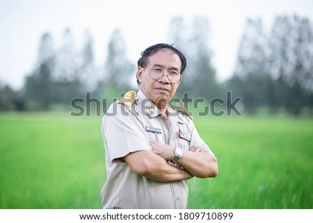 Portrait of Thai old man wearing formal teacher uniform with arm crossed and looking at camera on blurry nature background.
