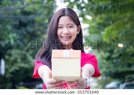 Portrait of thai teen beautiful girl in Chinese dress, happy new year and give gift, relax and smile.