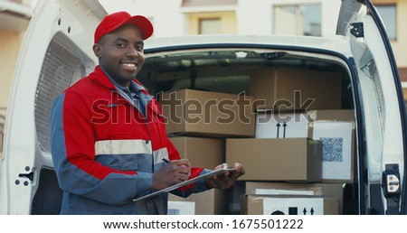 Portrait of the african American young male worker of shipping company standing at the van with boxes and writing the document, then smiling to the camera. Outdoors. Stock photo ©