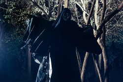 Portrait of the angel of death, grim reaper while standing in a mystical wood at night.