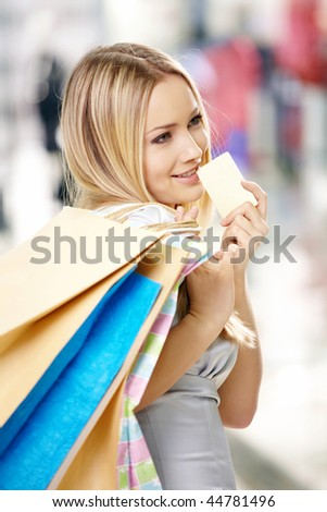Portrait of the attractive thoughtful blonde with bags and a credit card in shop