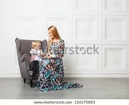 Portrait of the beautiful blond mother with little daughter in armchair
