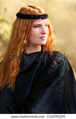 Portrait of the beautiful blonde girl in black dress