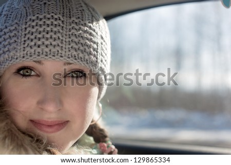 Portrait of the beautiful girl at a window in the car