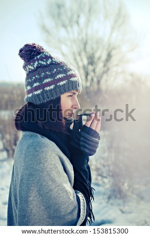 Portrait of the beautiful girl drinking hot tea in snowy winter