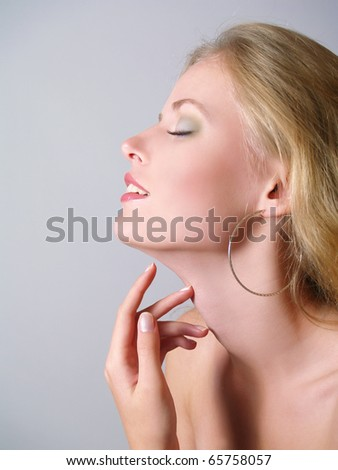 Portrait of the beautiful girl gently touching with fingers to a neck