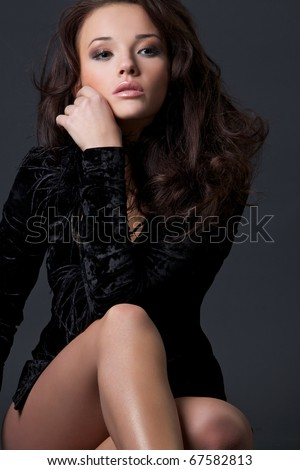 Portrait of the beautiful girl in a black velvet dress with wavy hair.