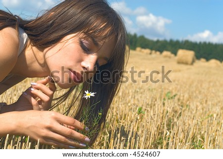 Portrait of the beautiful girl in a field with flower