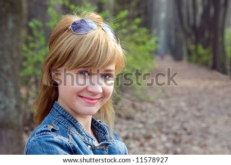 Portrait of the beautiful girl on a background of wood avenue.