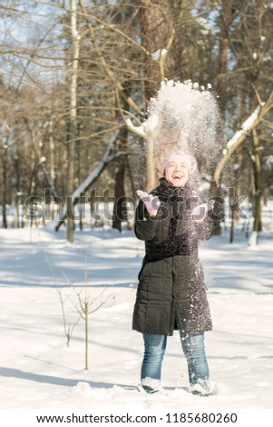Portrait of the beautiful girl throwing snow in the winter. Happy young woman plays with a snow in sunny winter day. A girl throwing snow in winter snow. Vertical photo