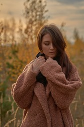 Portrait of the beautiful sensual woman in a coat in the autumn forest.