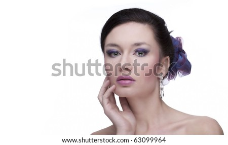 Portrait of the beautiful, sensual, young caucasian black-haired woman with silver earrings and blue and violet flower in her hair, on white isolated, a lot of copyspace and textspace