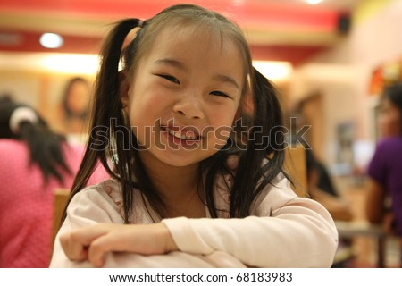 Portrait of the beautiful small Asian girl kid in the ice cream shop. Lampang Thailand