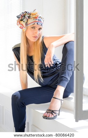 Portrait of the beautiful woman. Fashionable blonde is sitting at the window