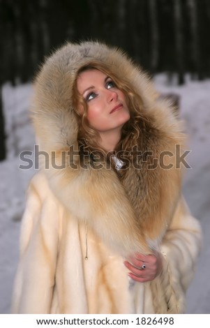 Portrait of the beautiful woman in the fur coat of the fox and mink