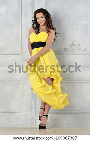 Portrait of the beautiful woman in yellow evening dress. Studio photo.