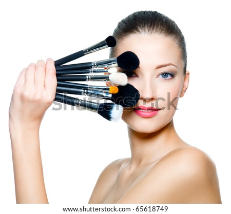 Portrait of the beautiful woman with make-up brushes near attractive face. Adult girl posing over white background