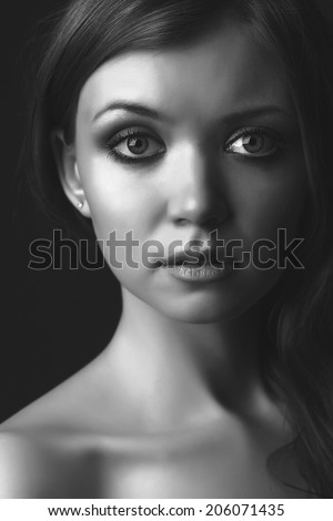 portrait of the beautiful young girl against a dark background. face is close. big eyes