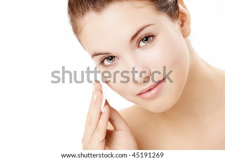 Portrait of the beautiful young girl applying on a face a cosmetic pad, isolated