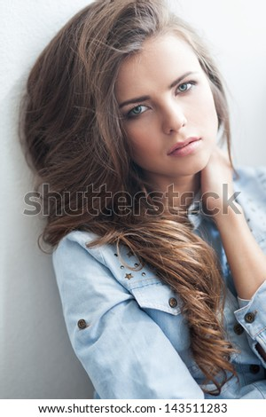 Stock Photo portrait of the beautiful young girl with long brown hair in studio