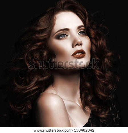 portrait of the beautiful young girl with red hair on a black background in studio