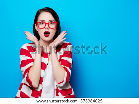 portrait of the beautiful young surprised woman on the blue background #573984025