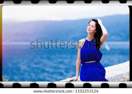 portrait of the beautiful young woman sitting on the stone railing in Greece . Image made with old film frame. Zdjęcia stock ©