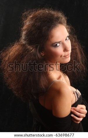 Portrait of the beautiful young woman with a magnificent hairdress on a black background.