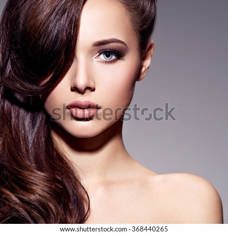 Stock Photo Portrait of the beautiful  young woman with long brown  hair posing at studio over dark background