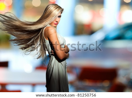 Portrait of the blonde with  flyaway hair in the background of city