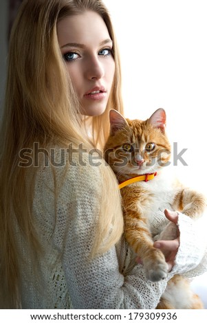Portrait of the blonde woman with cat near window