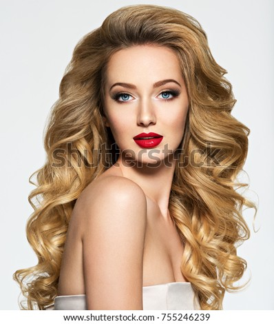 Portrait of the blonde woman with long  hair and red lips. Fashion model with bright makeup.