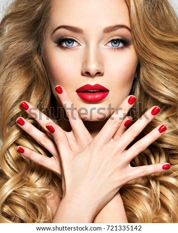 Portrait of the blonde woman with long  hair and red nails. Fashion model with bright makeup.