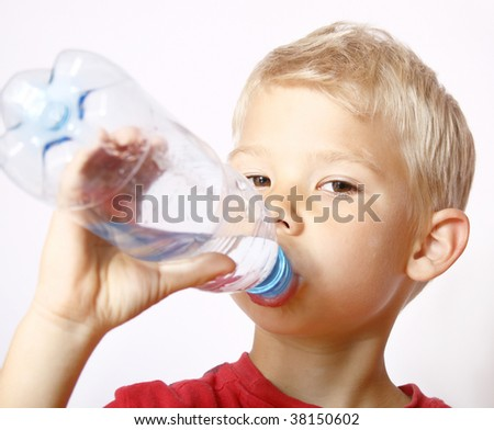 Portrait of the boy drinking water from a bottle.
