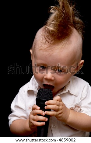 Portrait of the boy, singing in a microphone, with a ridiculous hairdress