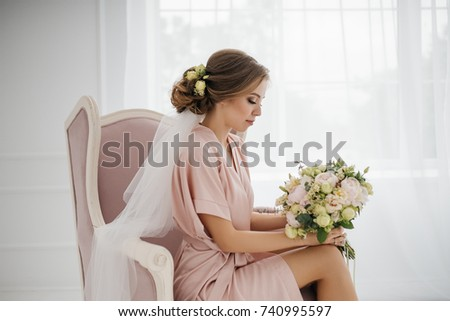 Portrait of the bride gathering in the morning near the window. In a pink robe in a white room with a pink armchair. #740995597
