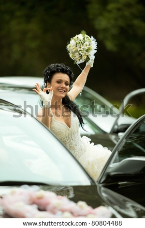 Portrait of the bride near the car showing 'ok' gesture