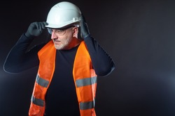 Portrait of the Builder on a dark background. A man in an orange vest puts a white construction helmet on his head. Construction uniforms. Jobs at the construction site. Place for text.