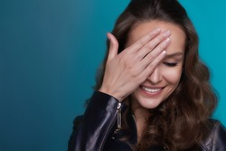 Portrait of the curly beautiful shy girl with shining  white teeth and dark hair hiding one eye and smiling on a blue background in leather jacket